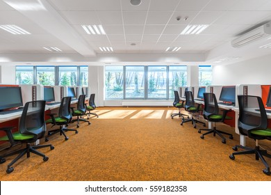 Spacious IT classroom with orange flooring and window wall