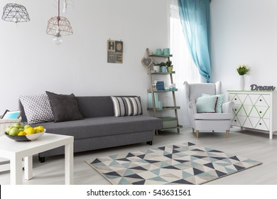 Spacious and comfortable living room with grey sofa coffee table and armchair