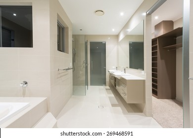 Spacious contemporary bathroom with spa and walk in robe