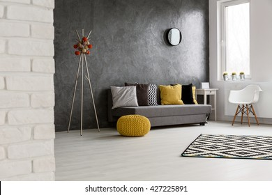 Spacious cozy grey living room with wooden bright floor. By the wall sofa with colorful pillows
