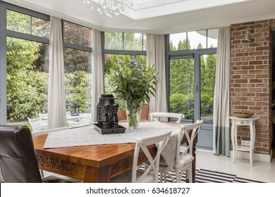 Spacious dining room surrounded by windows with wooden table and chairs in the middle