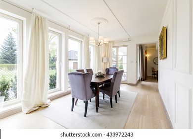 Spacious dining room with table, chairs big windows and decorative details