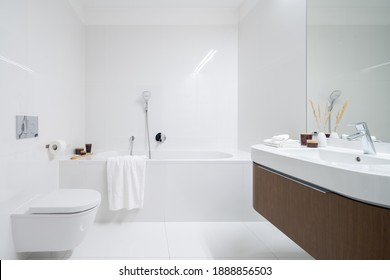 Spacious and elegant bathroom with big bathtub, white tiles, washbasin with wooden cabinet with drawer and big mirror