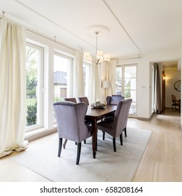 Spacious elegant dining room with table, chairs, big windows and decorative details