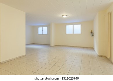 Spacious empty cellar. It is composed of windows and the light tiled floor. On the right there is a radiator and a light on the ceiling.