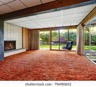 Spacious and empty living room has accent red wall to wall carpet and fireplace with beige tile surround. Wall of windows allows the natural light to flood in and boast well manicured back yard.