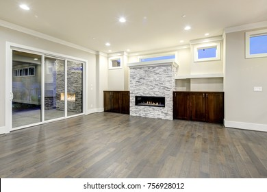 Spacious empty living room interior in white and gray colors accented with stone fireplace, wooden cabinets, gray hardwood floor and glass patio doors. Northwest, USA.