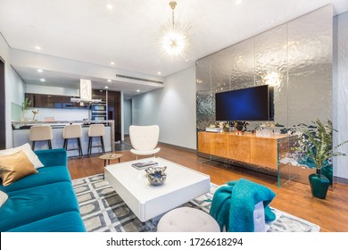 Spacious and fashionable light living room with connected dining area. Bright blue sofa, white armchair, coffee table and TV