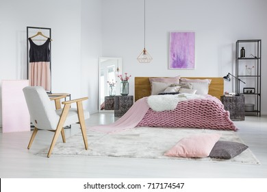 Spacious, feminine bedroom interior with cozy woolen blanket and pink tulle dress