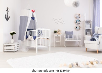 Spacious and full of light infant room with white furniture and marine decorations