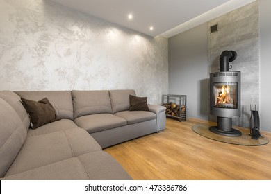 Spacious grey living room with large sofa, fireplace and venetian stucco