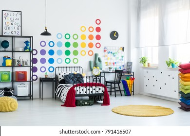 Spacious kid room with dots pattern decoration and grey knot pillow on the bed