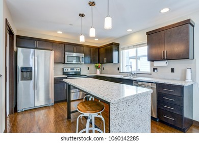 Spacious kitchen with open floor plan features chocolate brown cabinets and an island with granite counter top.