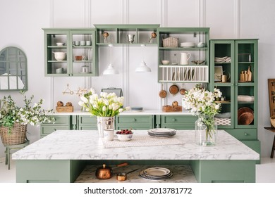 Spacious kitchen with vintage design, counter with marble top and flowers in metal bucket on it, organized furniture with various crockery, comfortable apartment interior
