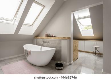 Spacious light attic bathroom with new large bathtub