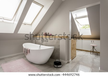 Spacious light attic bathroom with new large bathtub