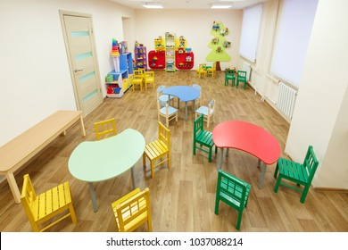Spacious light pink colored game room with tables for classes in the kindergarten.