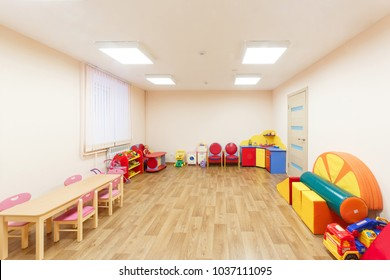 Spacious light pink colored game room with in the kindergarten.