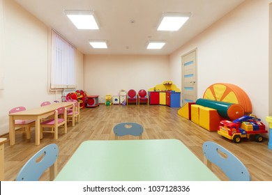 Spacious light pink colored game room with in the kindergarten. Table for classes on foreground