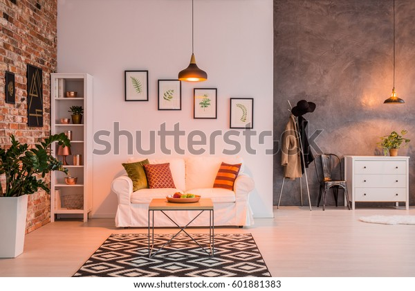 Spacious living room with brick wall, couch, table and lamp
