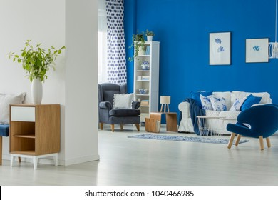 Spacious living room interior with blue armchairs, white couch and wooden coffee table with a lamp on it
