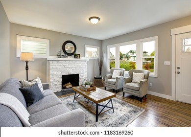 Spacious living room with traditional fireplace, grey sofa facing two armchairs and wood coffee table.