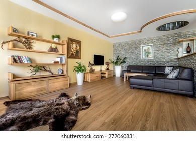Spacious living room with wood floors, ceiling lined with wooden furniture decorated with hunting trophies, leather seats and counter separating the kitchen.