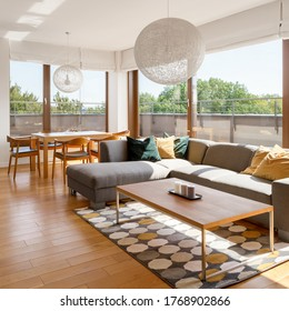 Spacious living room with wooden floor and big windows, gray corner sofa and wooden dining area