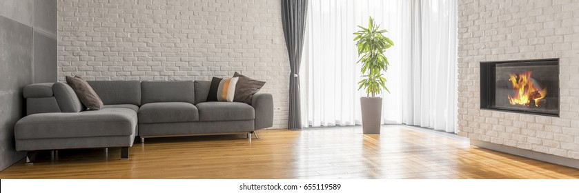 Spacious lounge with wooden floor, sofa and white brick wall