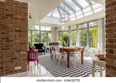 Spacious, modern dining room with windows around, glazed roof, stylish chandelier, brick walls and table with chairs in the middle
