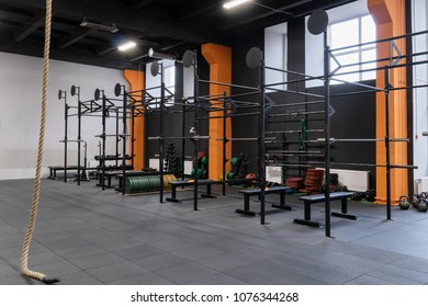 Spacious modern interior of the gym for fitness workout with horizontal bar, barbells and rope