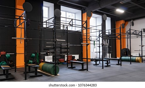 Spacious modern interior of the gym for fitness training with horizontal bar and barbells