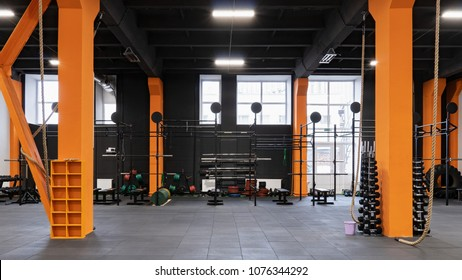 Spacious modern interior of the gym for fitness training with horizontal bar and rope