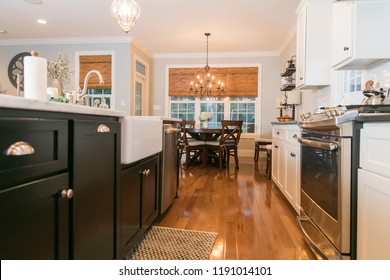 Spacious Modern Kitchen with Dark and White Cabinets Wood Floors Marble Island
