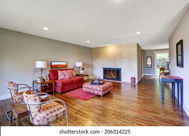 Spacious modern living room with bright red furniture and red rug on hardwood floor. View of fireplace built-in the brick wall