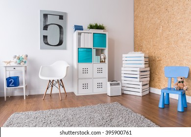 Spacious modern room for boy. In the corner boxes with toys and shelf with books