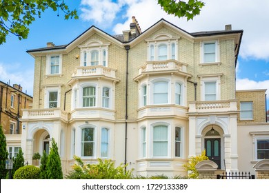 Spacious old traditional Victorian cream terraced house with brick facade with balconies and stone balustrades. Arch above the entrences. Concept of wealth and investment. London, UK 11/05/2020