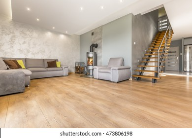Spacious open living room with extra large sofa, fireplace, venetian plaster and wooden stairs