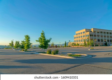 Spacious outdoor parking lot with a modern building and blue sky background