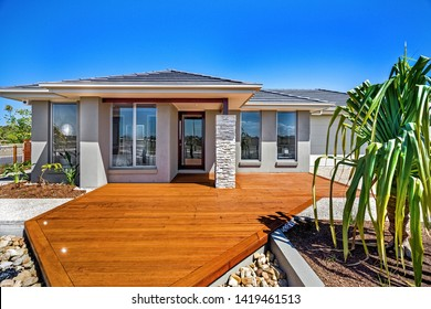 Spacious patio with wooden panel flooring and a house entrance