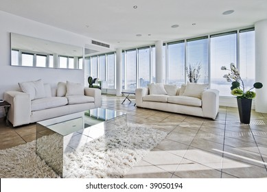 spacious penthouse living room with floor to ceiling windows and modern furniture