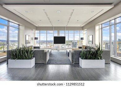 Spacious resident lounge in grey tones with stunning window view of Seattle. Northwest, USA