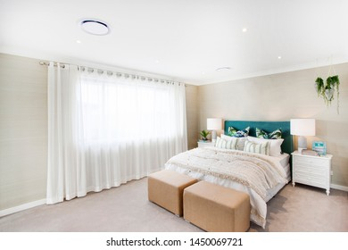 Spacious room with minimal furniture, stylish bed with two leather foot benches.