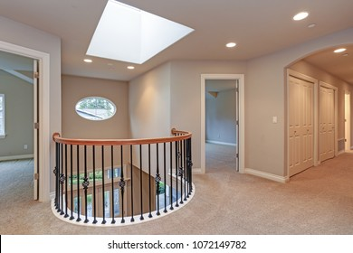 Spacious second landing with tan walls, skylight and black hand rails overlooking grand entrance foyer.