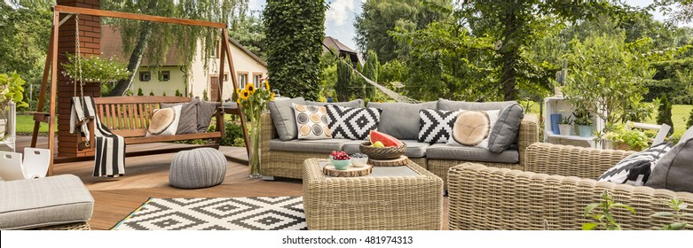 Spacious terrace with stylish garden furniture and wooden garden swing