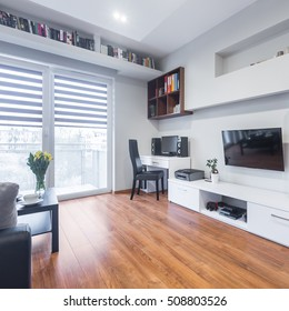 Spacious TV living room with balcony and white furniture