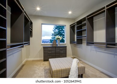 Spacious walk-in closet with clothes rails, shelves and ottoman over carpet floor.