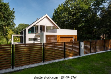 Spacious white house with wooden decoration on garage and wood style fence