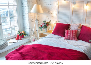 A spacious white light bedroom in a loft style with a decorated Christmas tree and a garland.