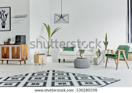 Spacious white room with pattern carpet, sofa and armchair